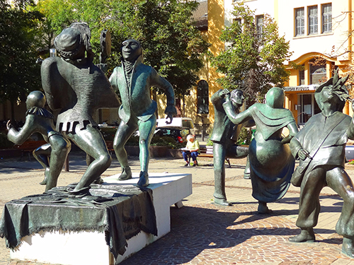 Statues of revelers on the Place du Théâtre