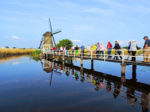 People crossing a bridge to a windmill