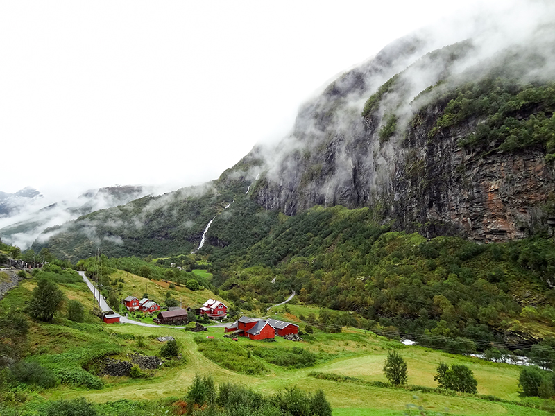 house in a valley below a large mountain seen during Norway in a nutshell