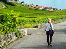 a woman walking through vineyards seen on a day trip from geneva