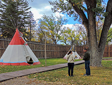 2 people by a teepee Inside Fort Benton MT