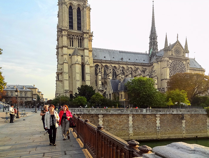 people passing Notre Dame during their walks in Paris