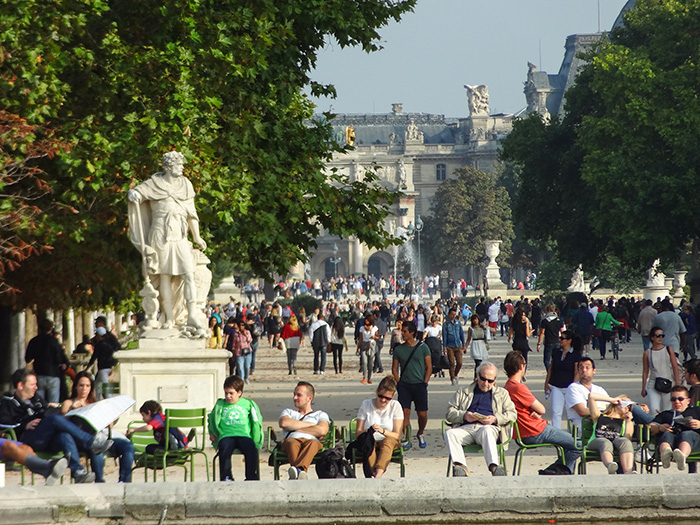 people sitting under a large statue in Paris