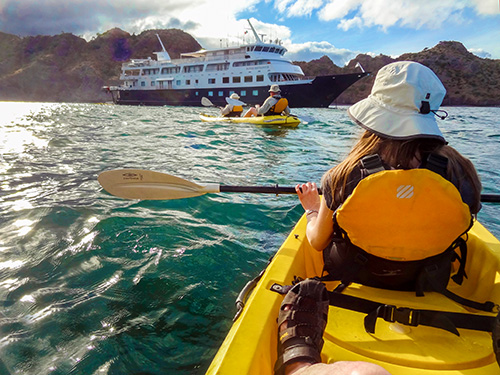 kayaks paddling towards a cryise ship in the Sea of Cortez