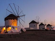 Four white windmills at dusk in Mykonos Town