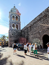 people walking by old building with a clock tower in Galapagos
