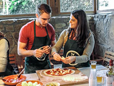 A couple standing and preparing a pizza in our cooking class in florence