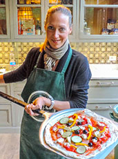 Woman holding pizza pie on an oven paddle during our cooking class in florence