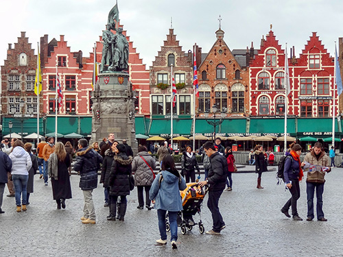 people at an outdoor market with old gabled buildings, one of the things to do in Bruges