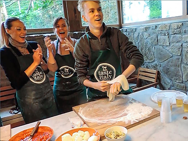 boy tossing pizza dough in a cooking class in Florence
