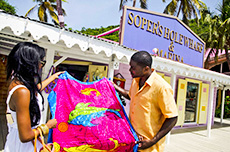 couple holding colorful towel outisde a shop