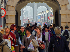 Crowd of people walking through an archway in Vienna