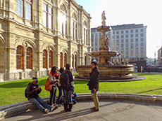 A group of people talking near a fountain by an ornate building in Vienna