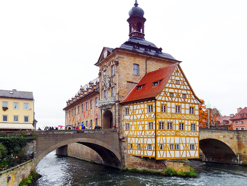 people on a bridge looking at old buildings in one of the best German towns to visit