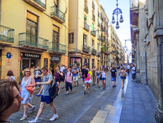 people walking along a street lined with old buildings in Barcelona