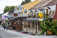 people walking through a charming old town near the Saguenay Fjord