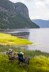 people in chairs sitting along the shore of the Saguenay Fjord