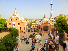 people by fanciful buildings in a park in Barcelona