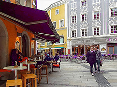 a couple walking past a cafe in Passau, one of the best German towns to visit