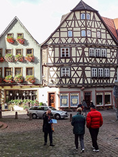 people walking by an old timber house in Wertheim