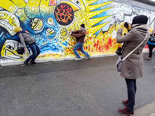 a couple being photographed in front of a large painted wall in Berlin