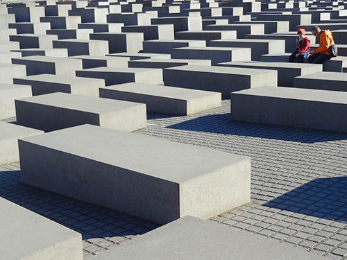 a couple sitting by a large memorial