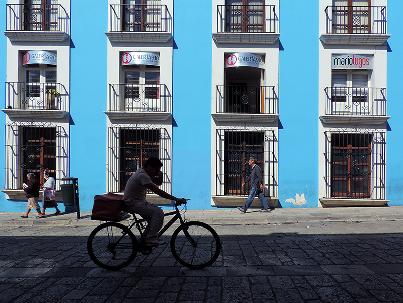 a boy riding a bike in front of a blue building, one of the things to do in oaxaca