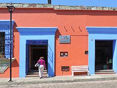 women walking into a colorful building in Oaxaca