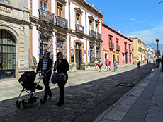 people walking along a colorful colonial street