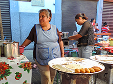 Women standing next to a large platter of street food in Oaxaca
