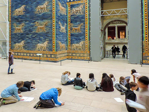 children on the floor in a museum drawing pictures of an exhibit in Berlin
