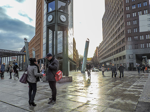 people on a city street with modern buildings