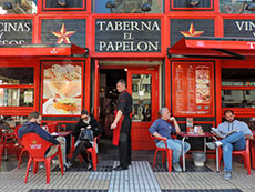 people sitting outside a brightly painted red bar in Seville