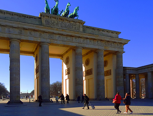 people walking through a large old city gate in Berlin