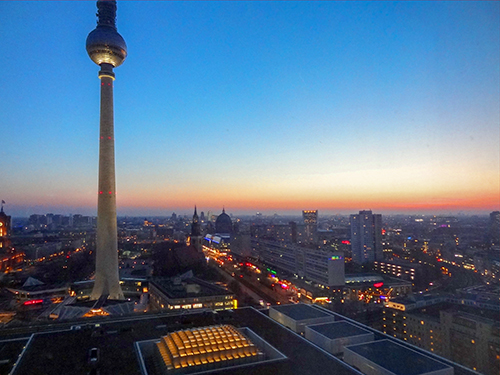 A tall television tower over a city at sunset