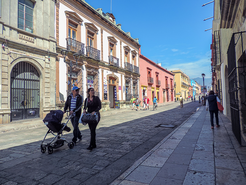 a couple pushing a baby carriage aong a street