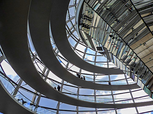people walking on ramps inside a glass dome, one of the things to see in Berlin