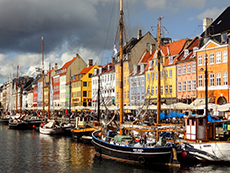boats at dock in front of colorful old buildings in Scandinavia