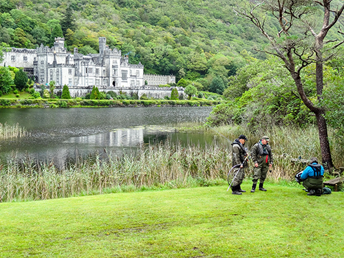 fisherman by a lake in front of an old Victorian mansion in Ireland