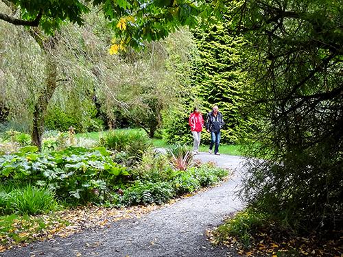 a couple on a path walking through a formal garden
