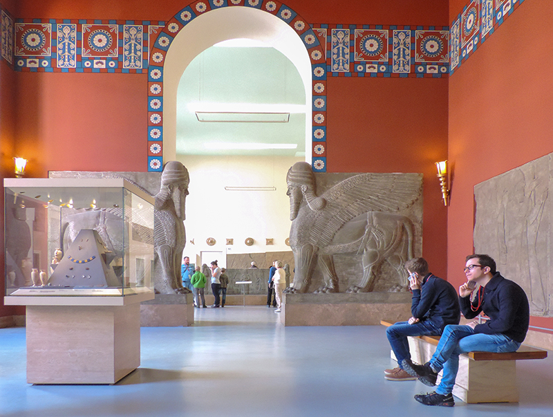 people sitting in a museum with large sculptures, one of the things to see in Berlin