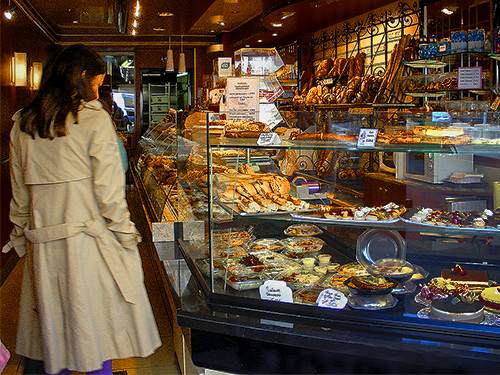 a woman looking at the display inone of the best Paris patisseries