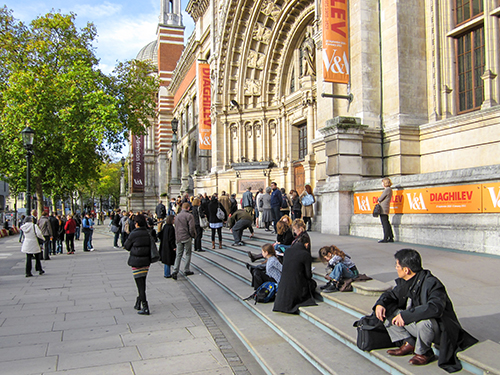 people sitting on the steps of one of the museums of South Kensington