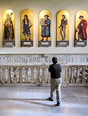 man looking at statues in a museum in London - London museum