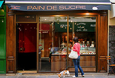 a woman looking into a pastry shop window