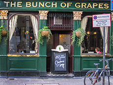 front of a green painted British pub in London - London museum