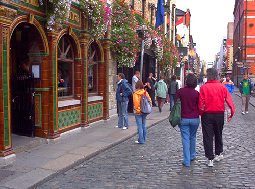 people walaaking along a cobblestone street with flowers on the buildings