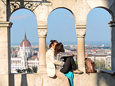 a couple sitting in an archway with a church dome in the distance