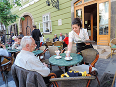 man at an outdoor cafe being served by a waitress in Budapest
