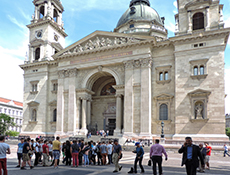 a crowd in front of a large Gothic basilica